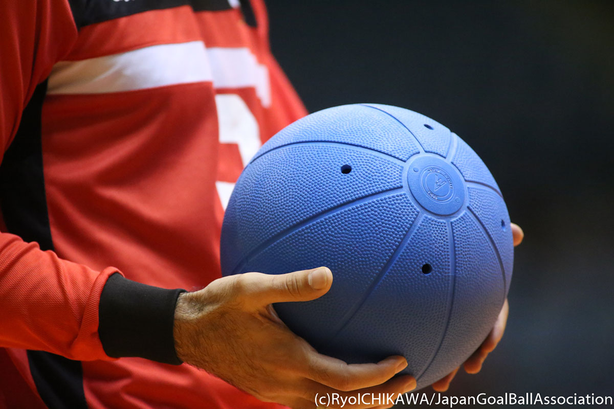 A player holds a goalball in his hands